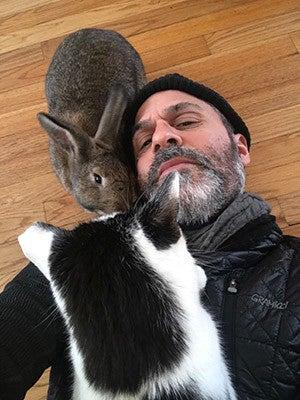 Kramnick posing with his pet bunny and pet cat.