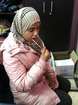 A young woman provides a DNA sample via cheek swab.