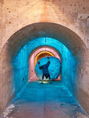 A performance piece by artist Aki Sasamoto depicting a woman standing on her hands in a blue-shaded tunnel.