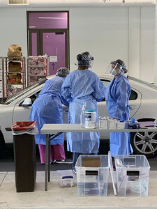Three health care workers in a drive-thru COVID-19 testing site.