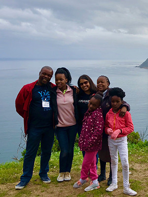 Monisha Merchant '04 M.B.A. (center) with Taona Tsopo, program panager for Amandla Development, and his family.