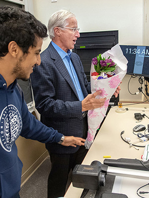 William Nordhaus accepts flowers from students on the day of his Nobel Prize award announcement.
