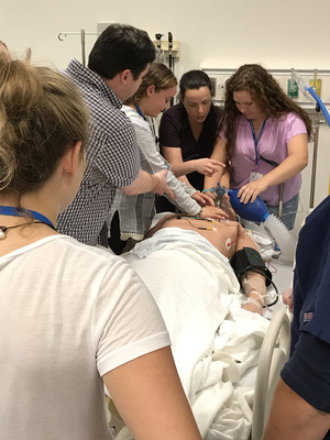 A group of people performing CPR on a medical test dummy.