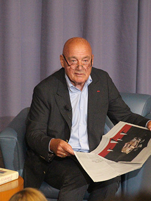 Pozner refers to a copy of the New York Times on stage at Luce Hall.