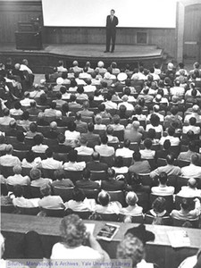 A black-and-white photo of Vincent Scully delivering a lecture to a large audience.