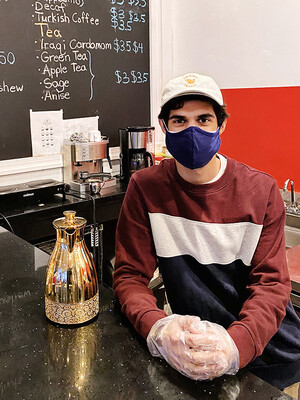 A man wearing a mask in a coffee shop.