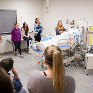 A nursing teacher using a manikin to demonstrate a technique for a room of students.