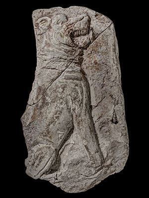 A terracotta plaque from ancient Mesopotamia which depicts a snarling mastiff wearing a collar.