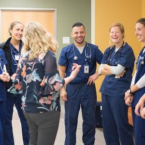 A group of nursing students in dark blue scrubs.