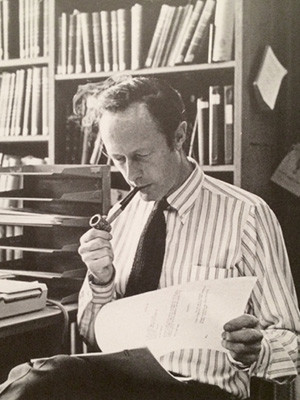 William Kelly Simpson reading and smoking a pipe.