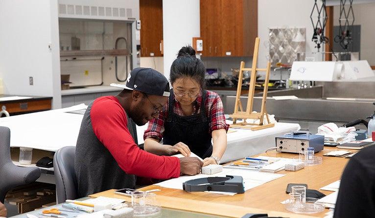 Soyeon Choi teaches Jordan Wright techniques for mending paper.