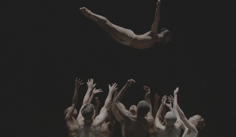 A dancer leaps into the arms of a group of other dancers against a black background.