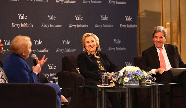 Hillary Clinton smiling on stage with Madeline Albright and John Kerry