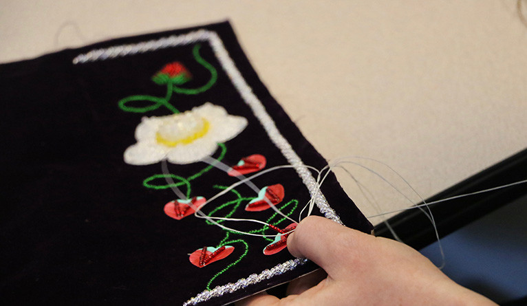 A person's hands as they sew a raised beadwork piece.