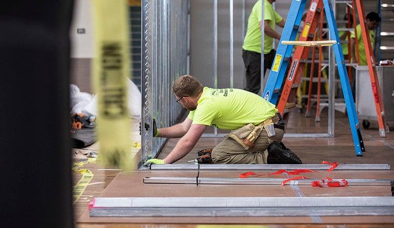 Workers build metal-framed rooms