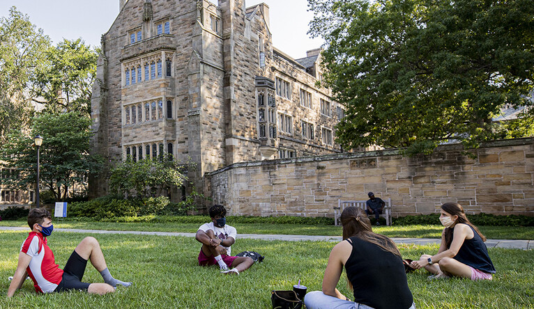 Students lounging on Cross Campus at a safe social distance, with masks on.
