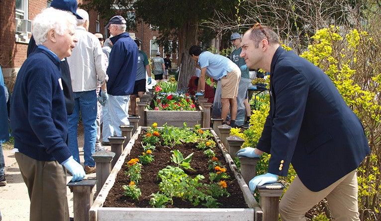Volunteers tending garden plots with veterans at the VA Connecticut Healthcare System in West Haven.