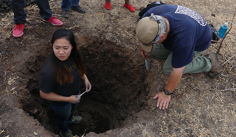 Annabelle Pan and Dave Sacco test soil compaction.