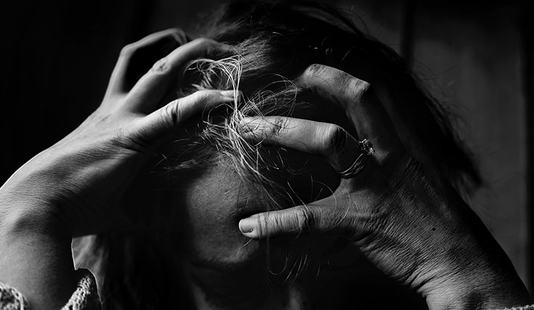 A black and white photo of a person clutching their head in stress.