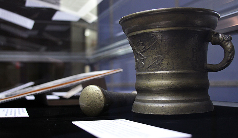 A mortar and pestle engraved with religious symbols.