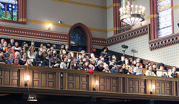An audience watching Cornel West deliver a lecture on the balcony at Battell Chapel.