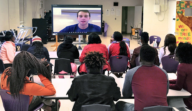 A group of teenage students watching a teacher on a large video chat screen.