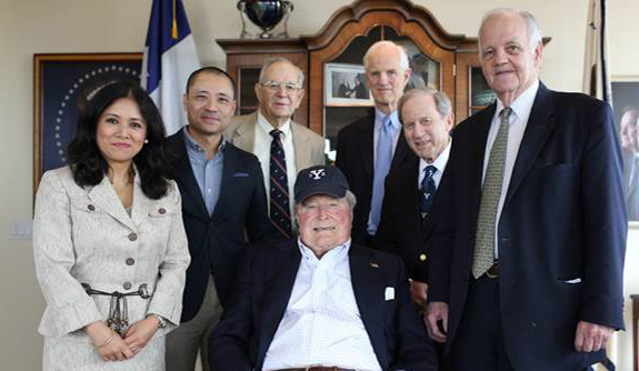 A group of Yale veterans pictured with George H.W. Bush, who is wearing the cap they presented to him.