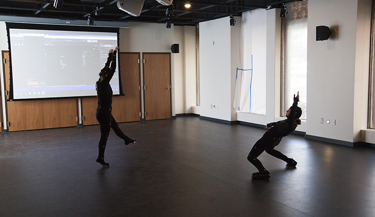Two people performing an interpretive dance while wearing motion capture suits.