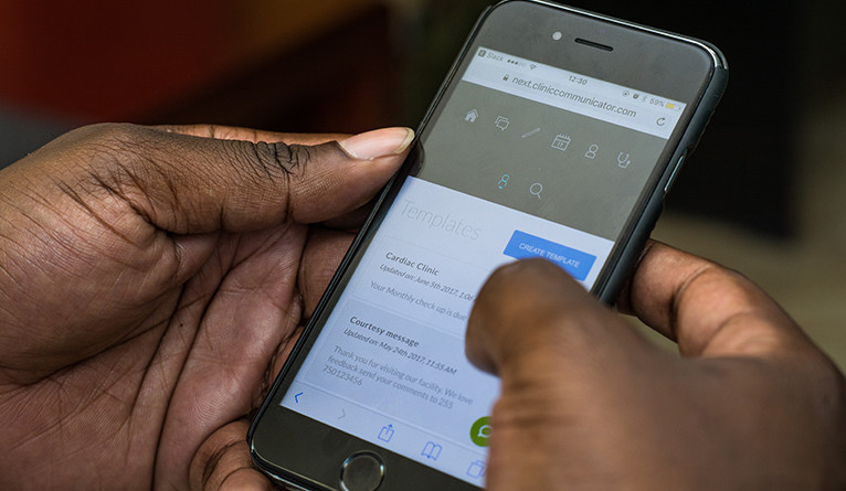 A closeup of a man using a smartphone app to receive a health notification from access.mobile.