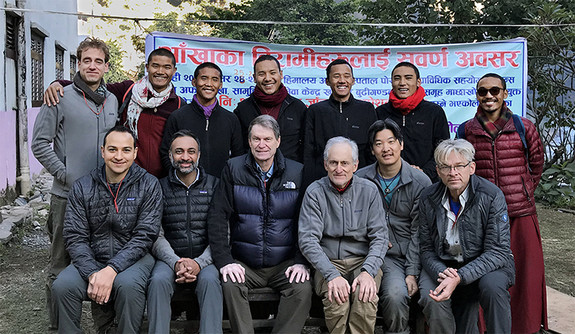 A group of doctors and local monks posing for a group photo in Nepal.