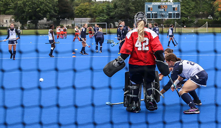Chaney Kalinich (In red) plays goalie with the Yale field hockey team at Johnson Field.