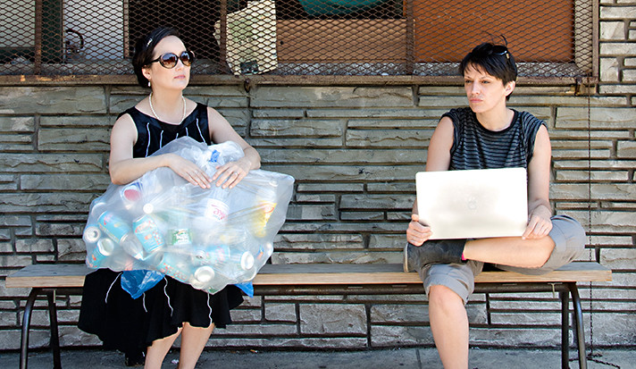 Two women sitting on a bench, one with a bag of garbage and the other with an expensive laptop.