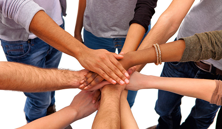 A diverse group of people putting hands in for a cooperative teamwork gesture