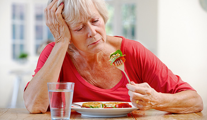 A women looking unhappily at a forkful of salad.
