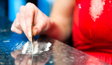 A woman cutting lines of cocaine on a table.