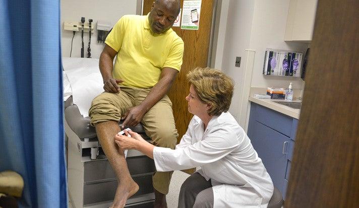 Dr. Katherine McKenzie examines a scar on refugee/asylum-seeker Paulin Kalonji's right leg.