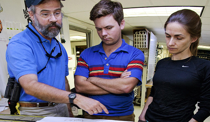 Researchers Richard Norris, left, Donald Penman, and Pincelli Hull study core samples of sediment from the North Atlantic.