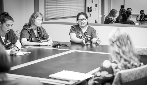 A black and white photo of nursing students in scrubs sitting at a table and talking.