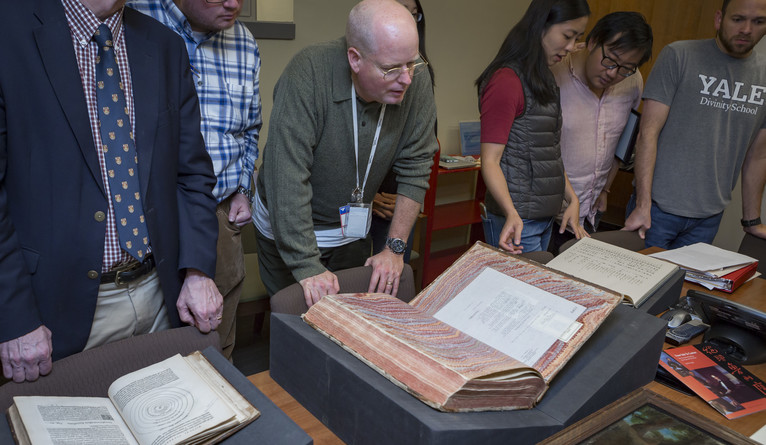 A professor and his students examining historical manuscripts.