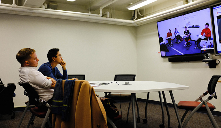 Two students watching a remote video feed of a language course through the Shared Course Initiative at Yale.