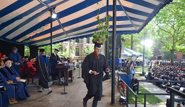 A marshal from School of Forestry & Environmental Studies descends the stage at Commencement with greenery on his mortarboard..