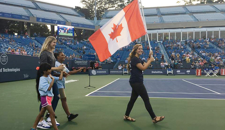 Yale student Leehi Yona carries the Canadian flag during the 2017 Opening Night Presented by Yale at the CT Open.