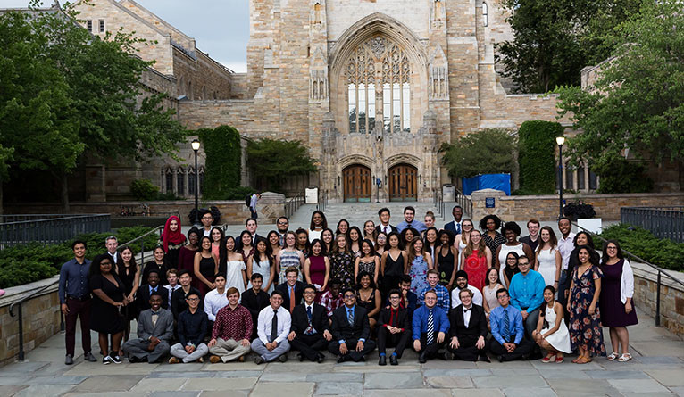 Members of the Class of 2021 who are particpating in First-year Scholars at Yale pose outside of the library.
