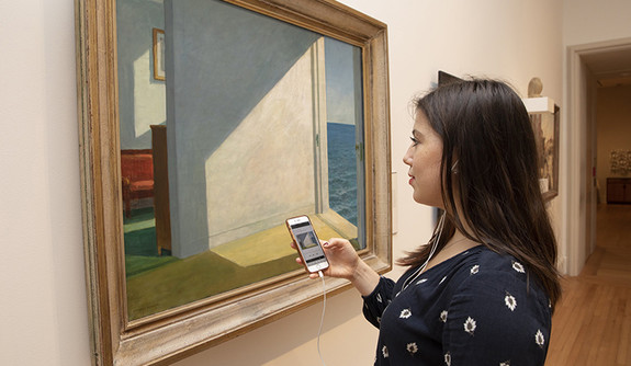 A woman in front of a painting by Edward Hopper, using a mobile app at the Yale art gallery.