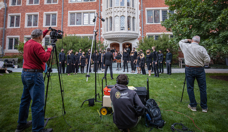 Film crew recording members of the Yale Glee Club, Yale Symphony Orchestra, and Yale Bands performing.