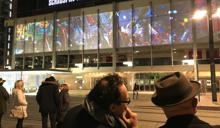 People watching an outoor video exhibition being projected onto the side of a building.
