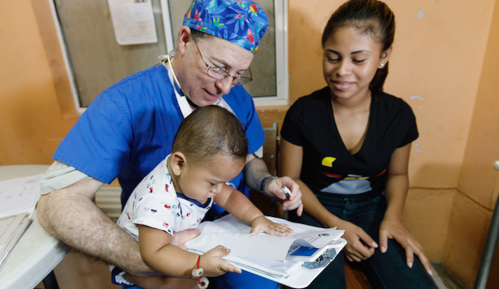 A surgeon in scrubs holds an infant in his lap while the mother looks on.