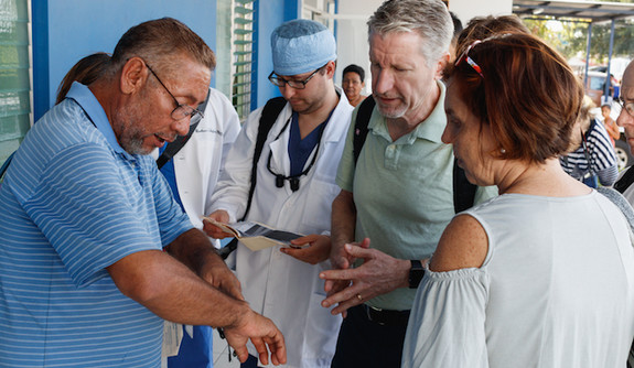 A patient points out the problem with his wrist to a medical team.