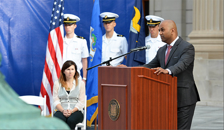 Speaker at podium with cadets in the background.