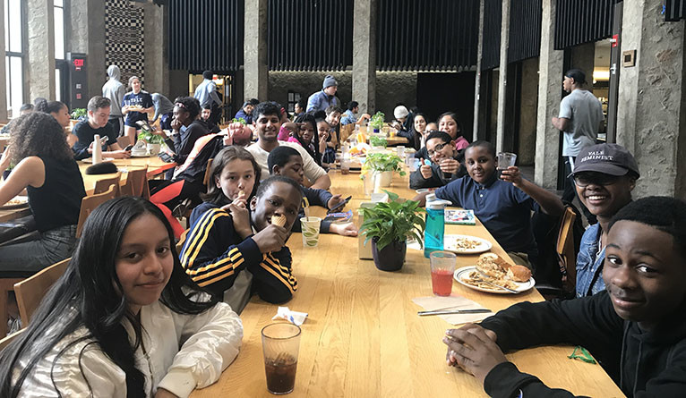 New Haven middle schhol students eating at the Ezra Stiles dining hall at Yale